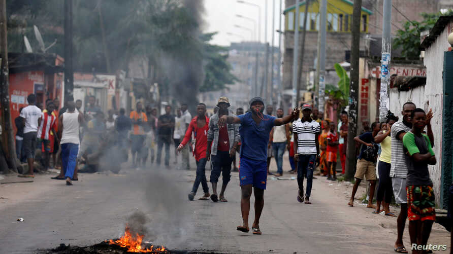 Residents chant slogans as they light a fire barricade in their neighbourhood in the streets of Democratic Republic of Congo's capital Kinshasa, Dec. 20, 2016.