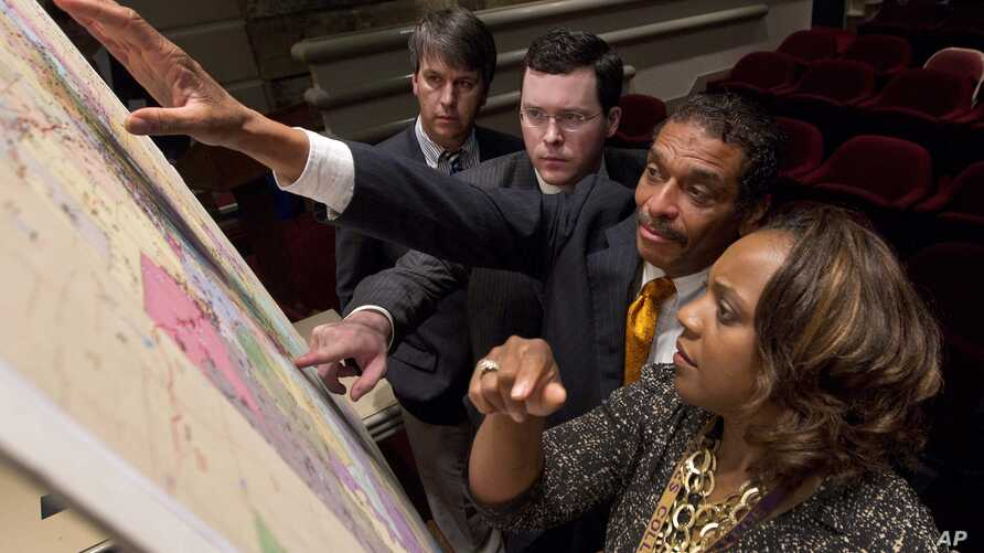 FILE - Lawmakers study a map of the proposed redistricting plan following a meeting of the Legislative Committee on Reapportionment at the Alabama Statehouse in Montgomery, Ala., May 9, 2012. The state's legislature approved new, court-ordered  elect...