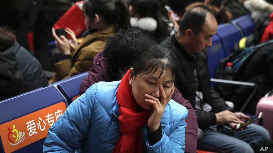 A woman reacts as she and travelers wait for their trains at the South Train Station in Beijing, Feb. 1, 2019. China is greeting the lunar new year with celebrations and a travel rush that will see an estimated 3 billion trips by people around the co