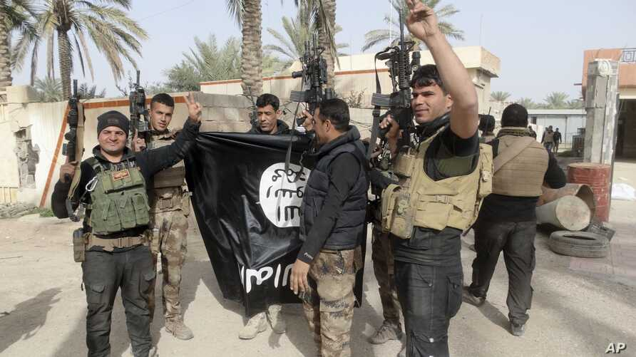 FILE - Iraqi security forces celebrate as they hold a flag of the Islamic State group they captured in Ramadi, 70 miles (115 kilometers) west of Baghdad, Iraq.