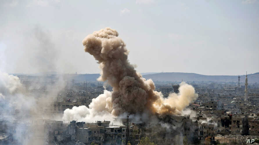 In this photo released by the Syrian official news agency SANA, smoke rises after Syrian government airstrikes and shelling hit in Hajar al-Aswad neighborhood held by Islamic State militants, southern Damascus, April 22, 2018.