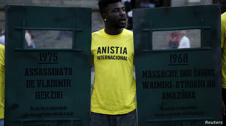 FILE - An Amnesty International activist shouts slogans in Rio de Janeiro, Brazil, April 1, 2014.