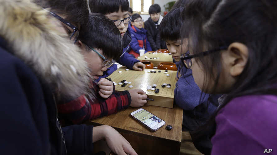 Elementary school children watch a smartphone screen showing the live broadcast of the Google DeepMind Challenge Match between Google's artificial intelligence program, AlphaGo, and South Korean professional Go player Lee Sedol, at Lee's Baduk Center