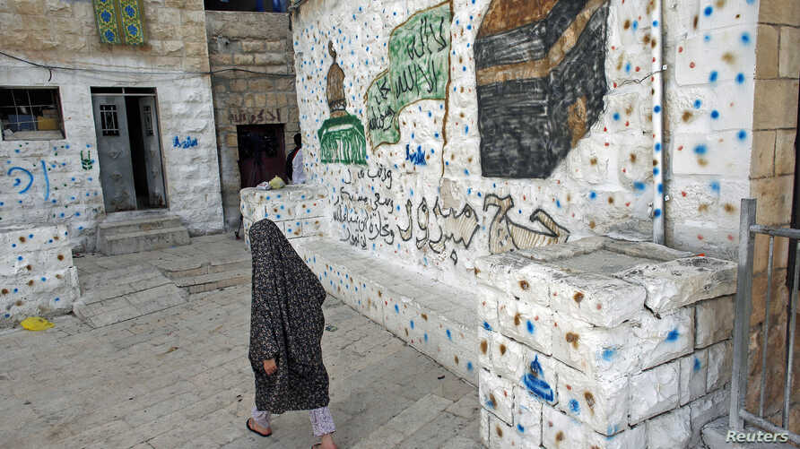 File - A Palestinian woman walks outside her home, next to a house (R) purchased by Jewish settlers, in the mostly Arab neighborhood of Silwan in east Jerusalem, October 2014.
