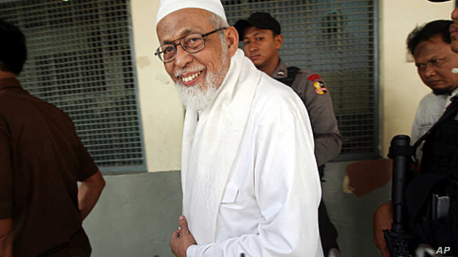 Militant cleric Abu Bakar Bashir walks from inside a holding cell to the start of his trial at a district court in Jakarta, Indonesia, June 6, 2011.