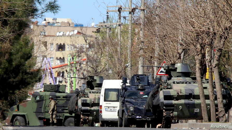 FILE - Military and police armored vehicles are parked in Baglar district, which is partially under curfew, in the Kurdish-dominated southeastern city of Diyarbakir, Turkey, March 17, 2016.