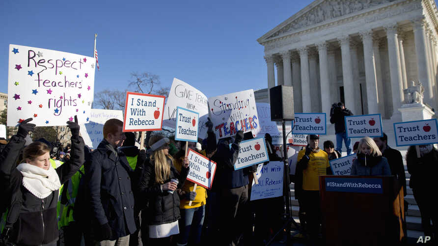 People participate in a rally at the Supreme Court in Washington, Jan. 11, 2016, as the court heard arguments in the 'Friedrichs v. California Teachers Association' case.