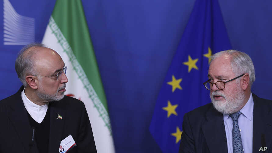Iran's Vice President and Head of the Atomic Energy Organisation Ali Akbar Salehi, left, looks at European Union Climate Action and Energy Commissioner Miguel Arias Canete during a joint news conference in Brussels, Nov. 26, 2018.