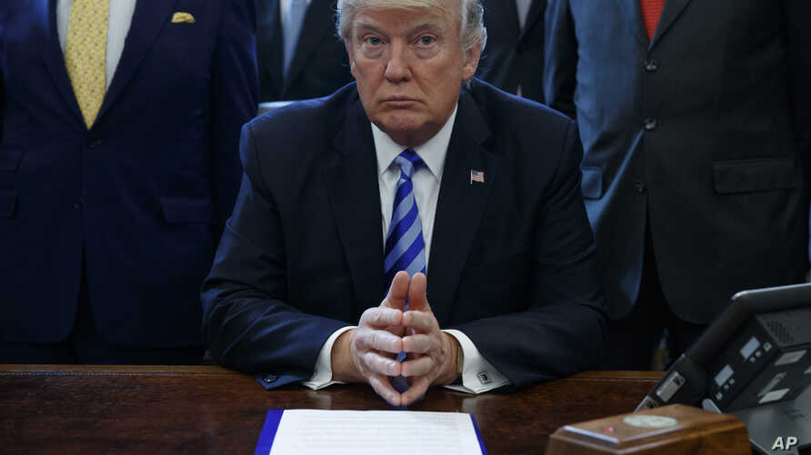 President Donald Trump pauses in the Oval Office of the White House in Washington, March 24, 2017, where it was announced the approval of a permit to build the Keystone XL pipeline, clearing the way for the $8 billion project, March 24, 2017.