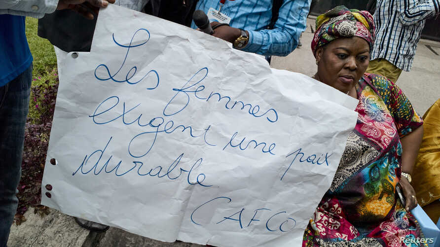 """FILE - A Congolese woman holds a placard saying """"Women require stable peace"""" as she and others sit in protest during talks between the opposition and the government of President Joseph Kabila outside the Conference episcopale nationale du Congo (CENC"""