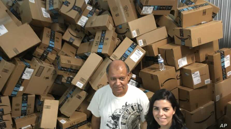 Catholic Charities of the Rio Grande Valley staffer Eli Fernandez and volunteer Natalie Montelongo pose for a photo as they stand by a pile of unsorted Amazon boxes packed with donations in McAllen, Texas, June 24, 2018.
