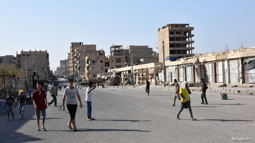 People walk along a street in Deir el Zour, Syria, in this photo provided by SANA, Sept. 11, 2017.