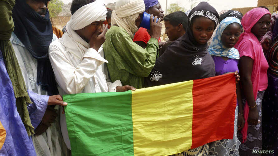 People seeking refuge from Tuareg separatist rebel group MNLA display a Malian flag in a military camp in the northern town of Kidal, July 17, 2013.