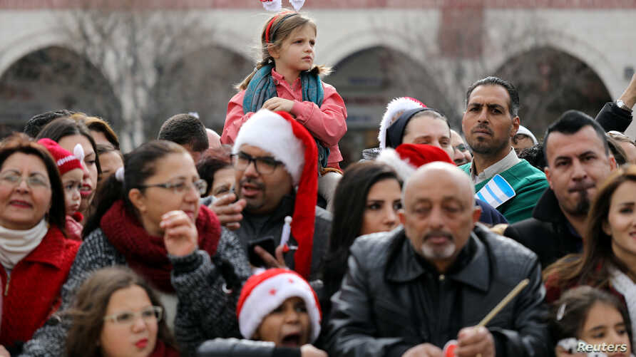 People attend Christmas celebrations outside the Church of the Nativity in the West Bank city of Bethlehem, Dec. 24, 2017.