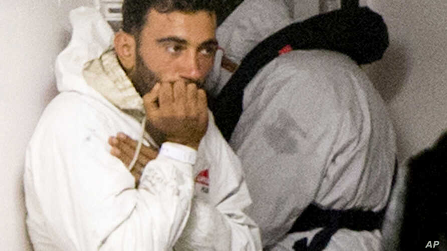 Tunisian navigator Mohammed Ali Malek, seen in this April 20, 2015 photo, and one of the survivors of the boat that overturned off the coast of Libya, wait to disembark from Italian Coast Guard ship Bruno Gregoretti, at Catania Harbor, Italy. A court