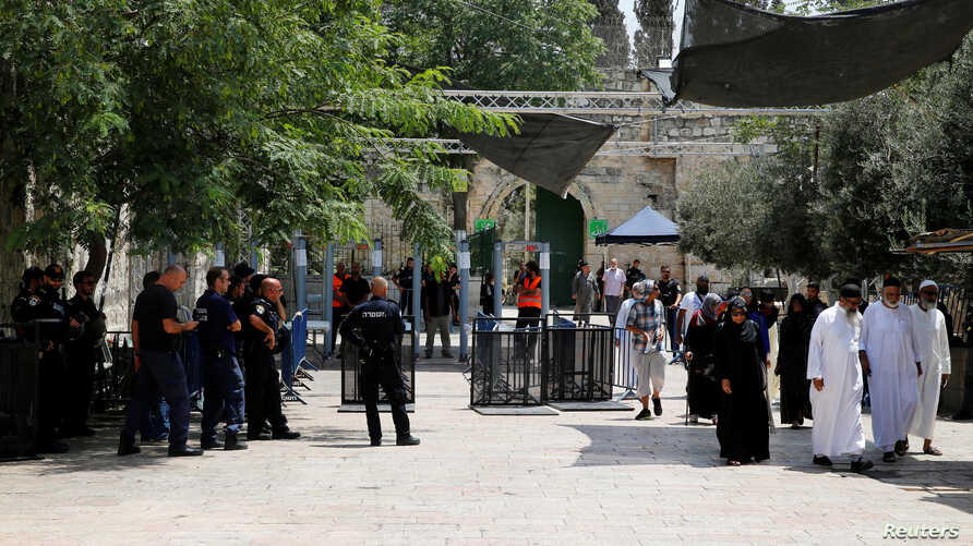 Tourists walk near Israeli police officers and recently installed metal detectors at an entrance to the compound known to Muslims as Noble Sanctuary and to Jews as Temple Mount in Jerusalem's Old City, July 23, 2017.