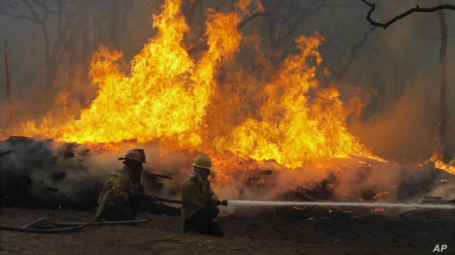 FILE - Firefighters battle a wildfire along Highway 71 near Smithville, Texas, Sept. 5, 2011.
