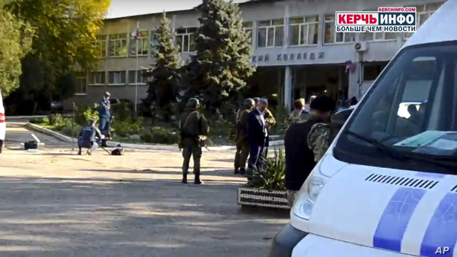 Policemen and investigators stand near a vocational school, in Kerch, Crimea, Oct. 17, 2018, following a shooting rampage.