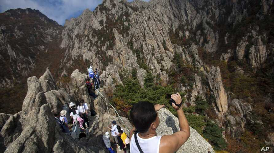 FILE – A North Korean man records video while climbing his country's Mount Kumgang in 2012. Some South Korean firms hope to resume a project involving tours to that area.