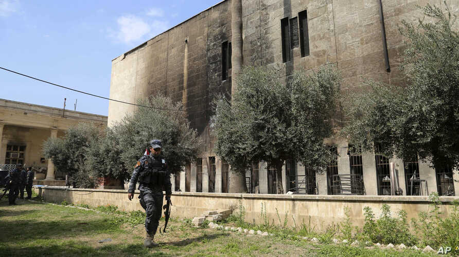 Iraqi federal police stand guard outside Mosul's heavily damaged museum, March 8, 2017. The facility was retaken from Islamic State forces on March 7.