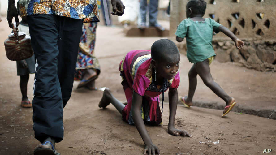 File--In this April 14, 2014 photo, Hamamatou Harouna, 10, crawls to the restroom on the grounds of the Catholic Church where she and hundreds of others found refuge in Carnot, Central African Republic.
