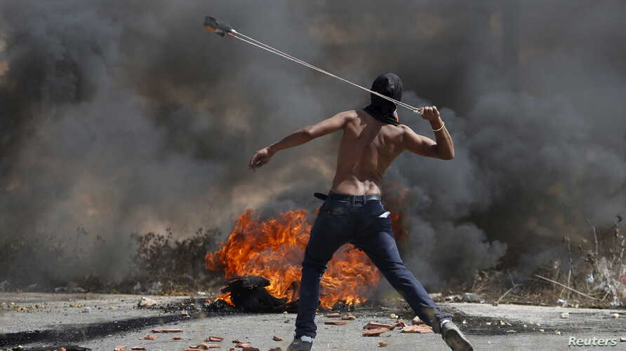 A Palestinian protester uses a sling to hurl stones toward Israeli troops near the Jewish settlement of Bet El, near the occupied West Bank city of Ramallah, Oct. 5, 2015.