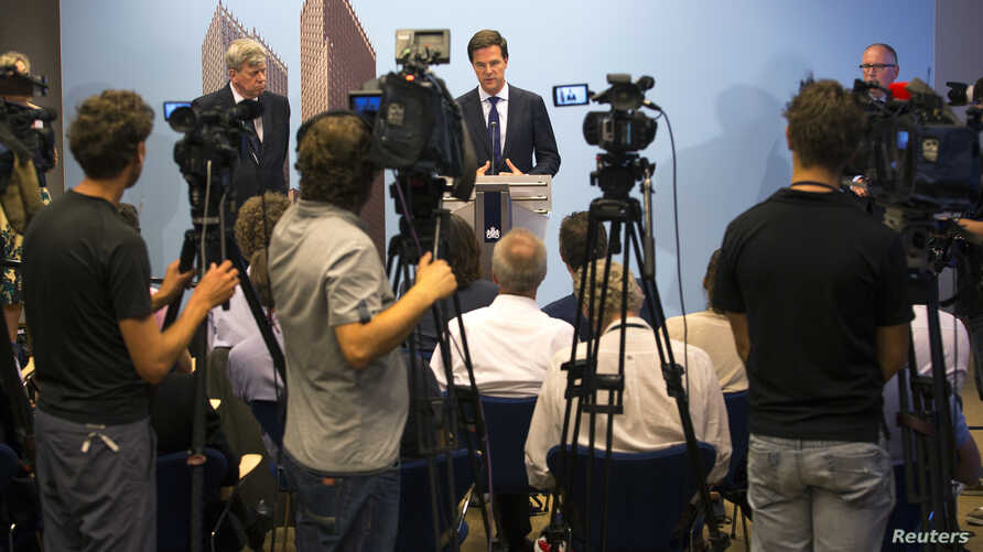 Netherlands' Prime Minister Mark Rutte (C) speaks, as he is flanked by Netherlands' Foreign Minister Frans Timmermans (R) and Justice Minister Ivo Opstelten (L) during a news conference at The Hague, July 18, 2014.