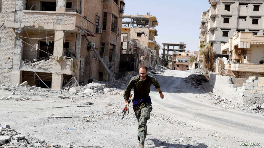 FILE - A British volunteer fighter of Syrian Democratic Forces runs for cover to avoid sniper fire of Islamic State militants, at the front line in Raqqa, Syria, Oct. 7, 2017.