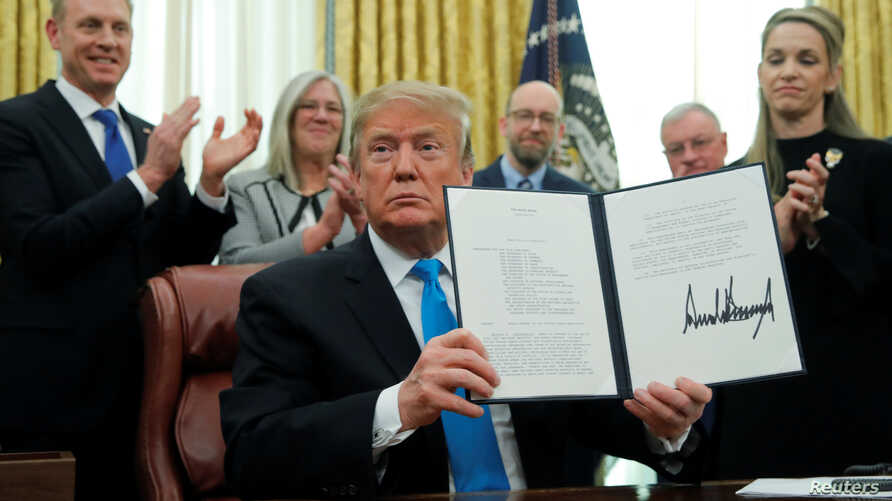"U.S. President Donald Trump displays the ""Space Policy Directive 4"" after signing the directive  to establish a Space Force as the sixth branch of the Armed Forces in the Oval Office at the White House in Washington, Feb. 19, 2019."