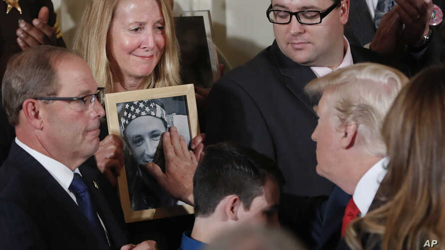 Jeanne Moser, center, of East Kingston, New Hampshire, watches as President Donald Trump reaches out to touch a photo of her son, Adam Moser, during an event to declare the opioid crisis a national public health emergency, in the East Room of the Whi
