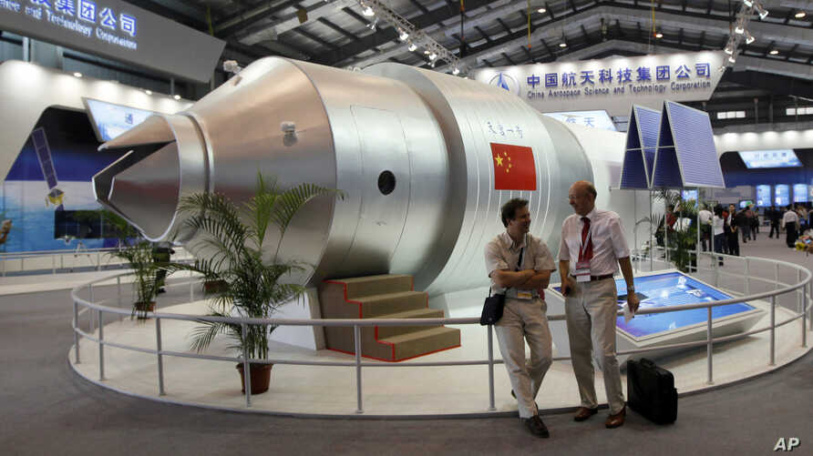 FILE - Visitors sit besides a model of Chinese made Tiangong 1 space station at the 8th China International Aviation and Aerospace Exhibition, known as Airshow China 2010, in Zhuhai city, south China, Guangdong province, Nov. 16, 2010.