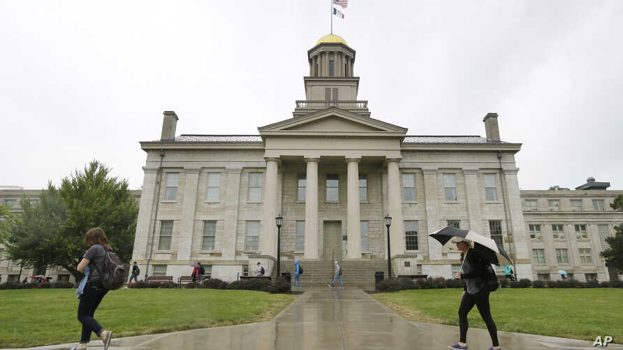 In this Oct. 2, 2014 file photo, students walk across campus at the University of Iowa in Iowa City, Iowa.