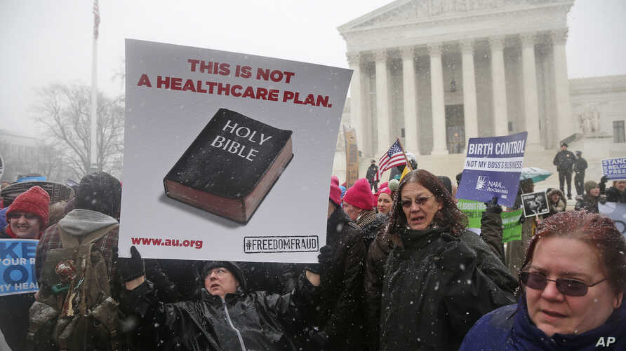 Beth Corbin holds a poster during a demonstration in front of the Supreme Court in Washington, Tuesday, March 25, 2014, as the court heard oral arguments  in the challenges of President Barack Obama's health care law requirement that businesses provi