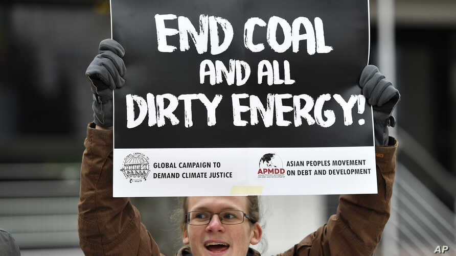 A protester holds a sign demanding to end coal burning during the 23rd Conference of the Parties (COP) climate talks in Bonn, Germany, Nov. 15, 2017.