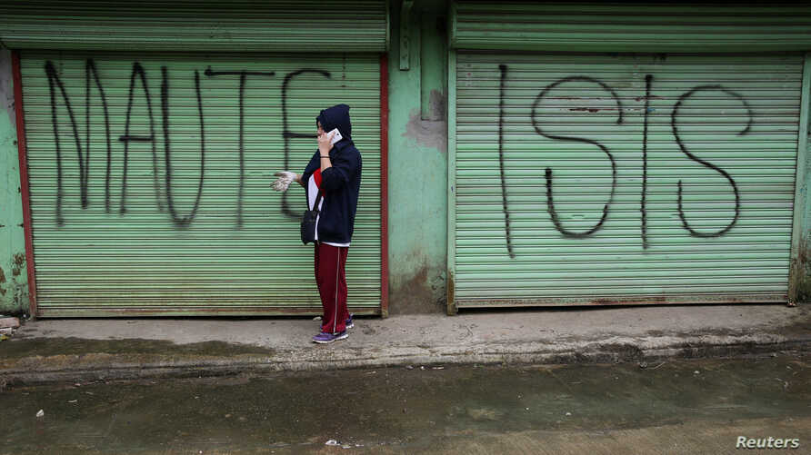 "FILE - A man is seen using a mobile phone while passing a shuttered store front with ""MAUTE-ISIS"" graffiti, in Marawi city, southern Philippines, Oct. 20, 2017. Maute, an Islamic State affiliate, was among groups the U.S. added to its terror list Tue..."