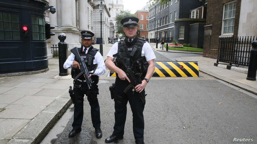 Armed police officers pose for the media in Downing Street, central London, Aug. 29, 2014.