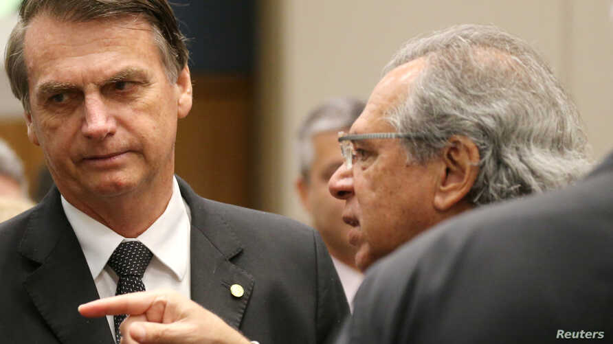 Federal deputy Jair Bolsonaro, left, a candidate for the Presidency of the Republic for the Social Liberal Party listens to economist Paulo Guedes before a lunch with businessmen at the Federation of Industries of Rio de Janeiro headquarters in Rio d