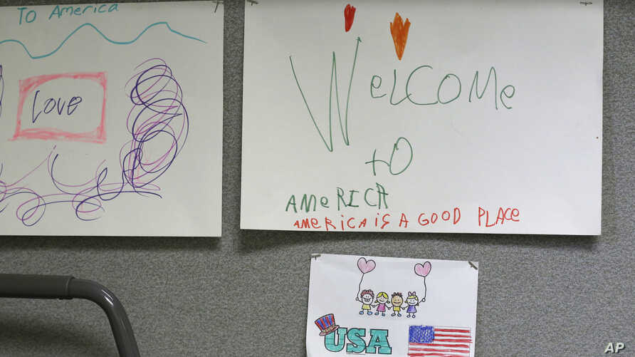 """Children's drawings that read """"Welcome to America, America is a good place,"""" are displayed April 24, 2017, at a Jewish Family Service Refugee and Immigrant Service Center in Kent, Wash., during a visit by Washington Gov. Jay Inslee."""