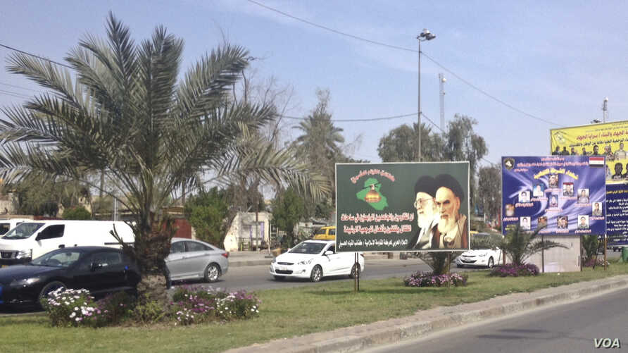A billboard image of Iranian Supreme Leader Ayatollah Ali Khamenei, left, and the late Ayatollah Khomeini is posted in the median of a busy road in Baghdad, Iraq, March 18, 2015.
