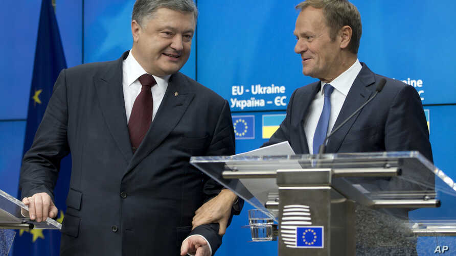 Ukrainian President Petro Poroshenko, left, speaks with European Council President Donald Tusk prior to a media conference at the conclusion of an EU-Ukraine summit, Brussels, Nov. 24, 2016.