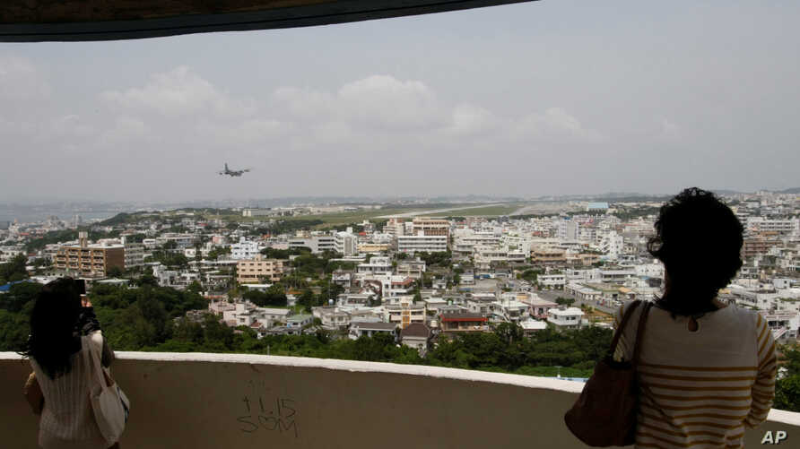 Visitors look out over U.S. Marine Corps Air Station Futenma in Ginowan on Okinawa, Japan, May 3, 2010. The Japanese and U.S. governments want the Futenma Air Base located in the middle of a crowded city moved to a sparsely populated area for safety