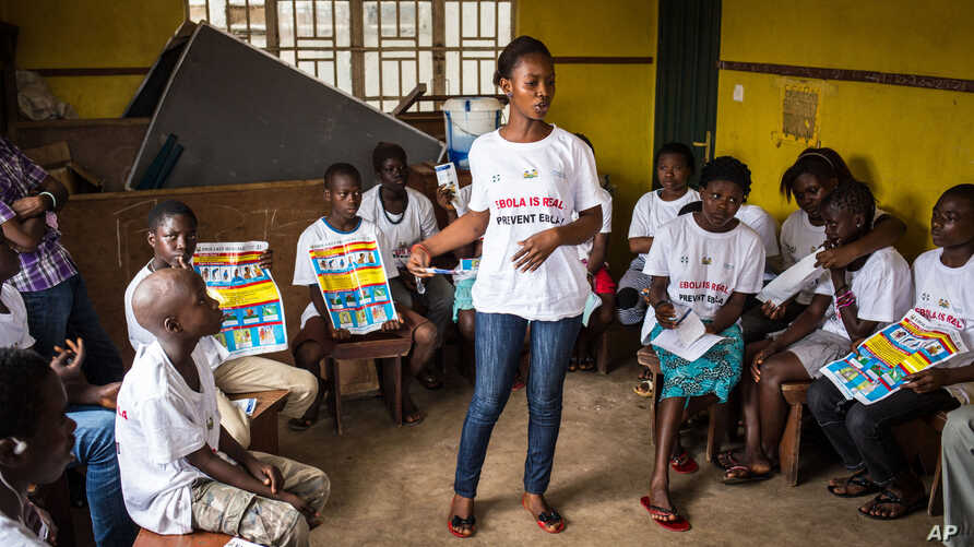 FILE -A charity worker, center, from the GOAL Ireland humanitarian agency, educates children on how to prevent and identify the Ebola virus in their communities at Freetown, Sierra Leone.