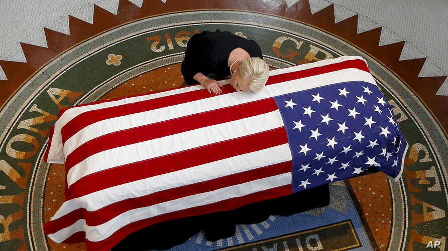Cindy McCain, wife of Sen. John McCain, R-Ariz., lays her head on casket during a memorial service at the Arizona Capitol in Phoenix, Aug. 29, 2018.