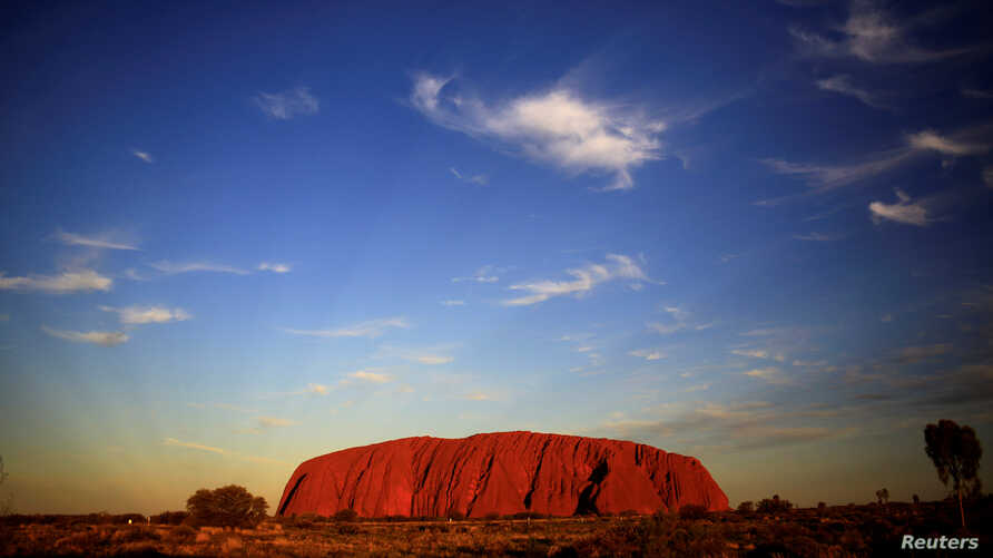 FILE: Uluru is lit by the setting sun in the Northern Territory in central Australia. April 21, 2014.