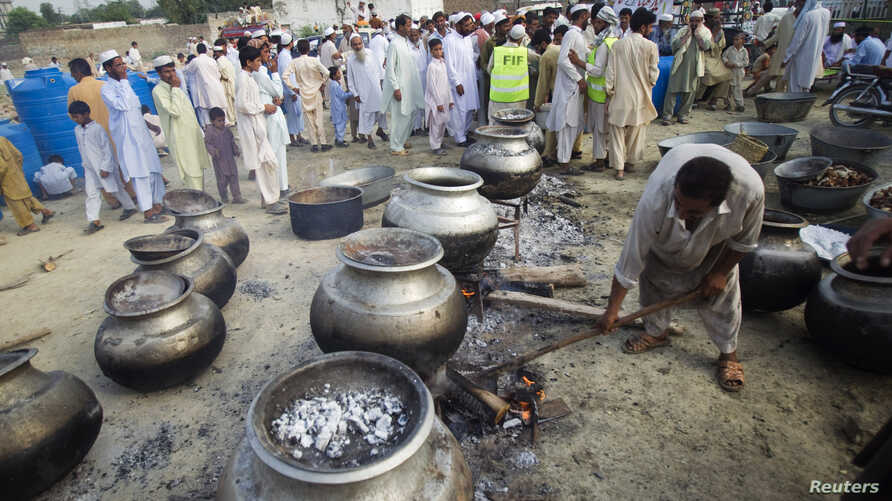 FILE - A Pakistani non-governmental humanitarian organization volunteer (front) adjusts a cooking fire as locals line up to receive meals in Nowshera, in Pakistan's northwest Khyber-Pakhtunkhwa Province, Sept. 10, 2010.