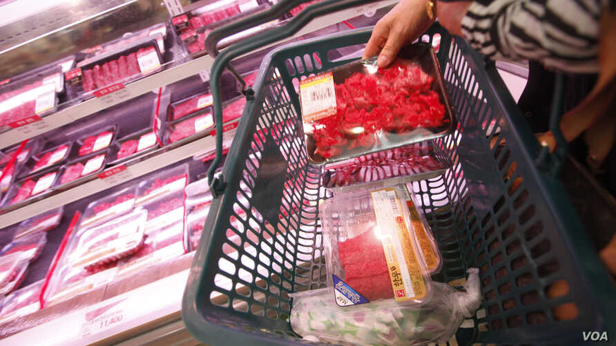 A woman picks up local beef at Lotte Mart in Seoul