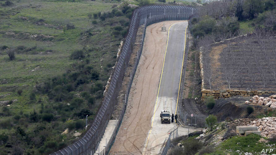 FILE - Israeli military vehicles patrol the border fence along the border with Syria, March 27, 2019.