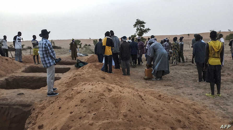 FILE - Officials and residents stand near freshly dug graves on June 11, 2019, in the Dogon village of Sobane-Kou, Mali, after an attack that killed over 100 ethnic Dogon on June 9, 2019.
