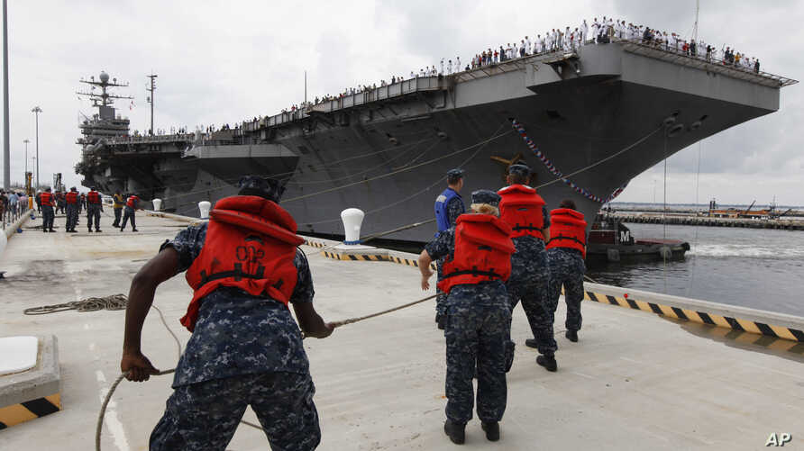 """FILE - Navy shore crew haul in lines as the USS Abraham Lincoln arrives at Naval Station Norfolk in Norfolk, Va., Aug. 7, 2012. The U.S. has dispatched the USS Abraham Lincoln and other military resources to the Middle East following """"clear indicat..."""