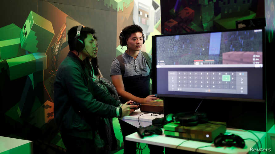 FILE - Gamers play Minecraft at the Paris Games Week (PGW), a trade fair for video games in Paris, France.